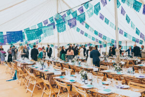 wedding reception in a marquee with blue bunting